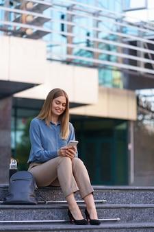 Joven profesional sentada en la escalera frente al edificio de cristal, hablando por teléfono móvil