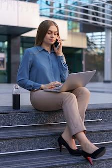 Joven profesional sentada en la escalera frente al edificio de cristal, sosteniendo el portátil en el regazo y hablando por teléfono móvil