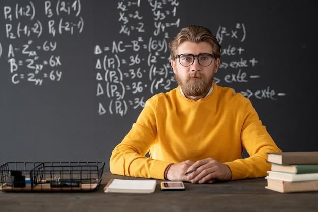 Joven profesor de álgebra barbudo sentado junto a la mesa en la pizarra con fórmulas y ecuaciones durante la lección en línea en el aula
