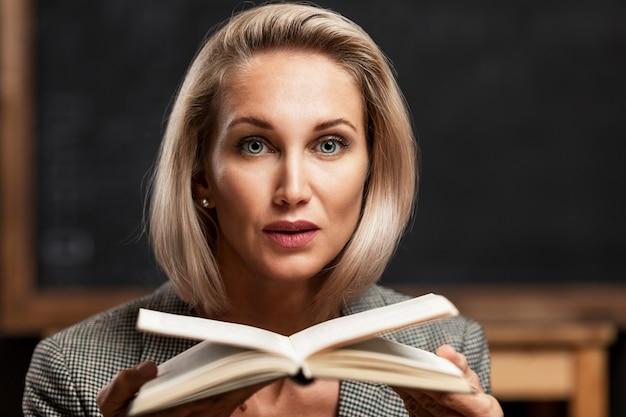 Joven profesor en el aula contra una junta escolar negra. una mujer rubia en un traje formal con un libro en sus manos. de cerca.