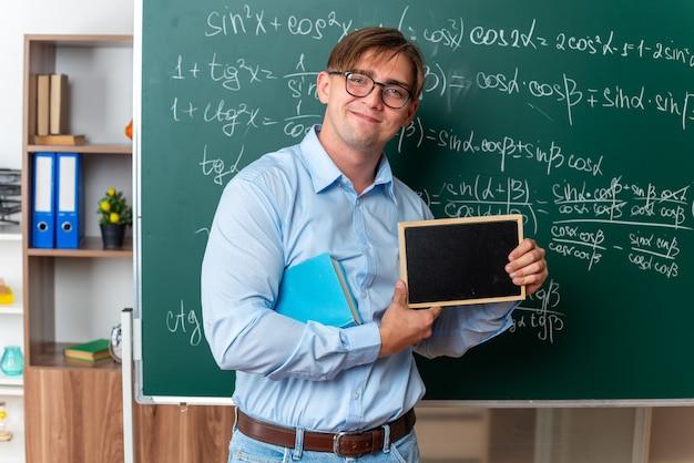 Joven profesor con gafas con libro sosteniendo una pequeña pizarra mirando a la cámara sonriendo confiados de pie cerca de la pizarra con fórmulas matemáticas en el aula