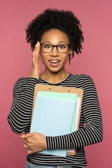 Joven profesor o tutor afroamericano feliz aislado en la pared rosa