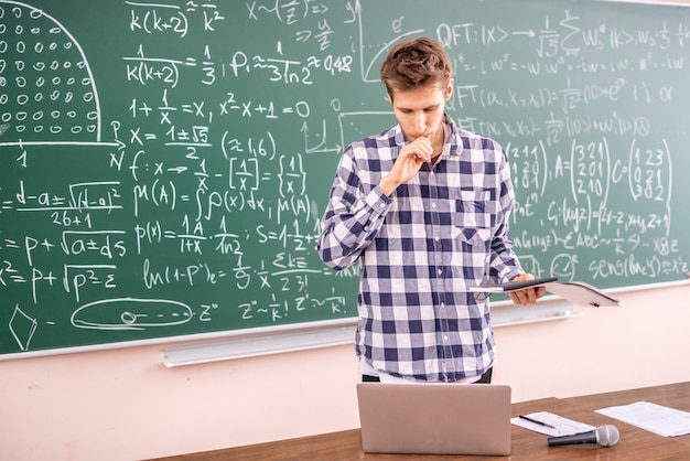 Joven profesor probando el teorema en una pizarra
