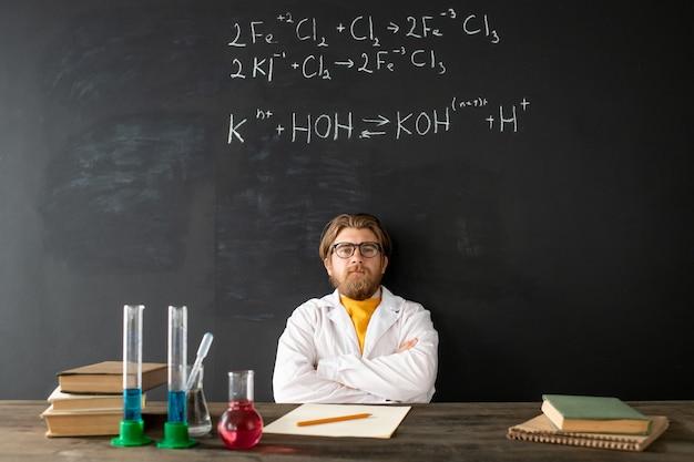 Joven profesor de química contemporánea en bata blanca cruzando los brazos sobre el pecho durante la lección en línea en la pizarra con fórmulas químicas