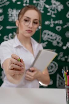 Joven profesor está sentado junto a la pizarra en el aula