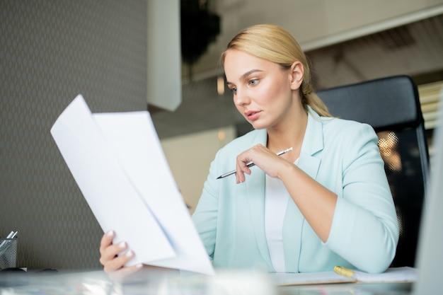 Joven profesor serio con lápiz mirando a través de los papeles de los estudiantes mientras los revisa