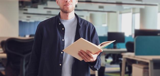 Un joven profesor en la universidad sosteniendo un libro en el aula