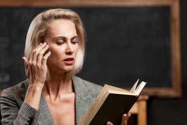 Joven profesora en el aula. una mujer rubia en un traje formal con un libro en sus manos. de cerca.