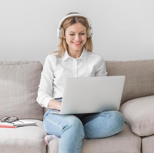 Joven profesora con auriculares preparándose para una clase en línea