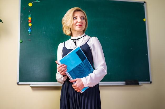 Joven profesora con una carpeta en el aula