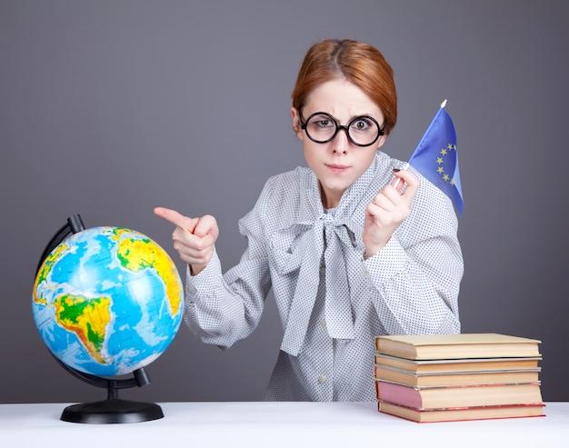 La joven profesora en copas con libros, globo y bandera de la unión europea.