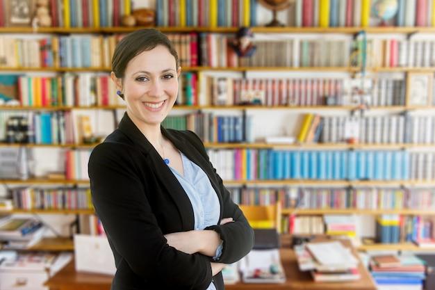 Joven profesora de pie frente a un librero
