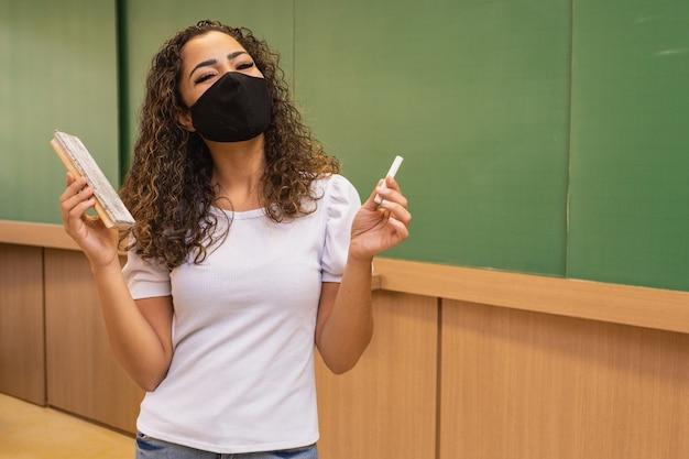 Joven profesora con tiza y goma de borrar en la mano con mascarilla quirúrgica en nueva normalidad.