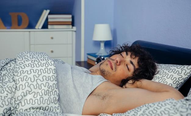 Joven profundamente dormido en la cama en casa