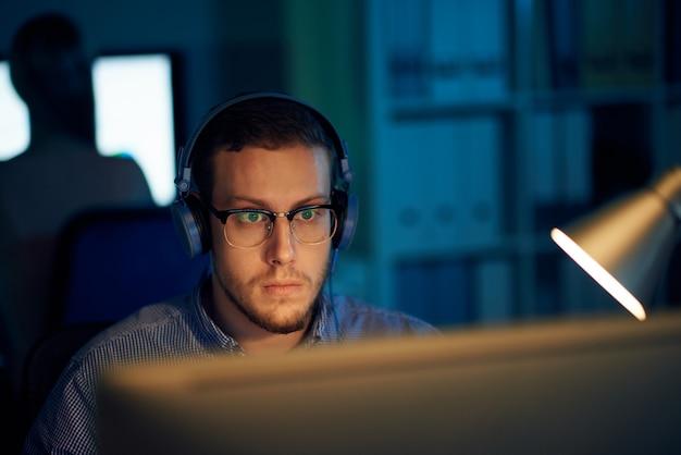 Joven programador en gafas y auriculares trabajando en oficina