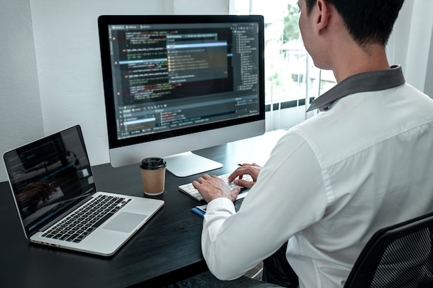 Joven programador que trabaja en software de computadora javascript en la oficina de ti