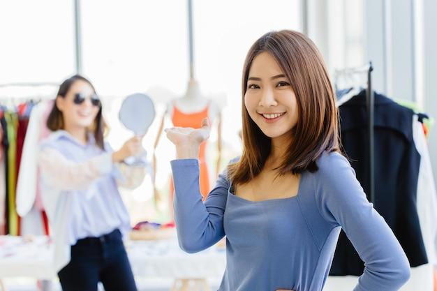 Joven propietaria de una pyme asiática feliz y orgullosa de presentar su tienda de ropa