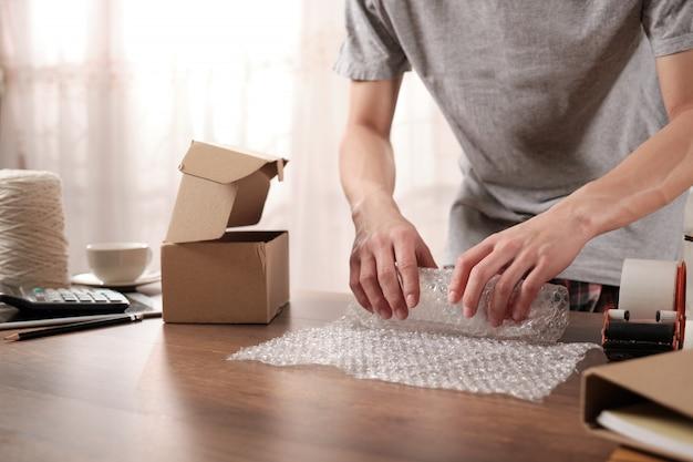 Joven propietario de una empresa de nueva creación que empaca productos en plástico a prueba de golpes para enviar al cliente