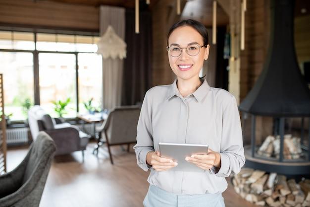 Joven propietario exitoso de un moderno restaurante o cafetería sosteniendo el panel táctil mientras hace el menú de la semana