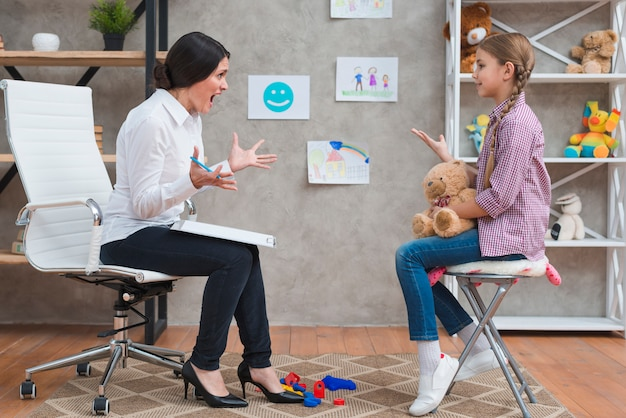Una joven psicóloga enojada que grita a la niña sentada con un oso de peluche