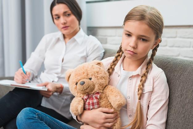 Joven psicóloga observando a la niña triste sentada con un oso de peluche.