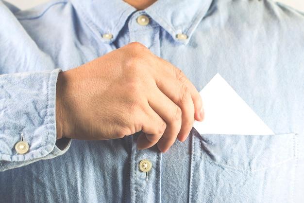 Joven que saca tarjeta de visita en blanco desde el bolsillo de su camisa