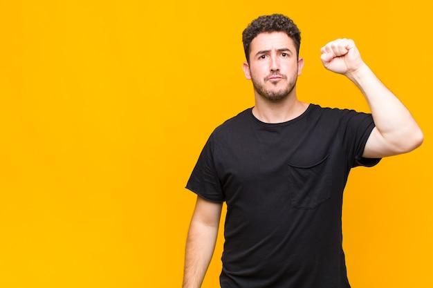 Joven que se siente serio, fuerte y rebelde, levanta el puño, protesta o lucha por la revolución