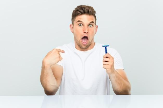 El joven que sostenía una cuchilla de afeitar se sorprendió apuntándose a sí mismo, sonriendo ampliamente.