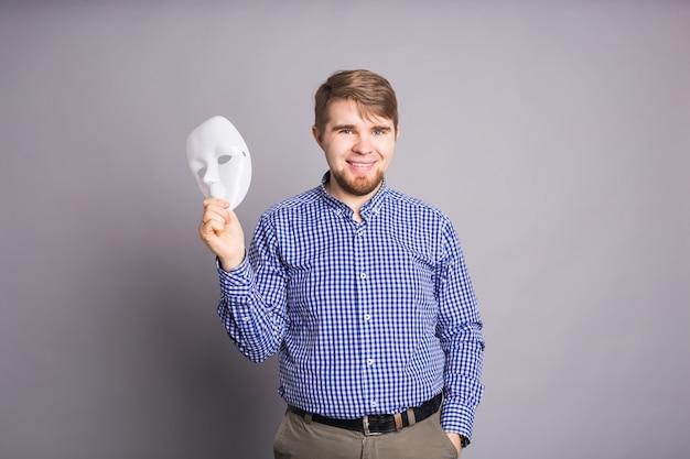 Joven quitándose la máscara blanca lisa que revela la cara, pared gris