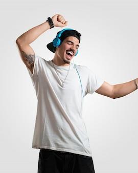 Joven rapero escuchando música, bailando y divirtiéndose.