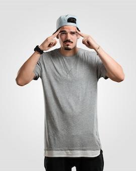 Joven rapero hombre hombre haciendo un gesto de concentración, mirando hacia adelante enfocado en una meta