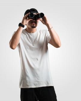 Joven rapero sorprendido y sorprendido, mirando con binoculares en la distancia algo interesante, concepto de oportunidad futura.