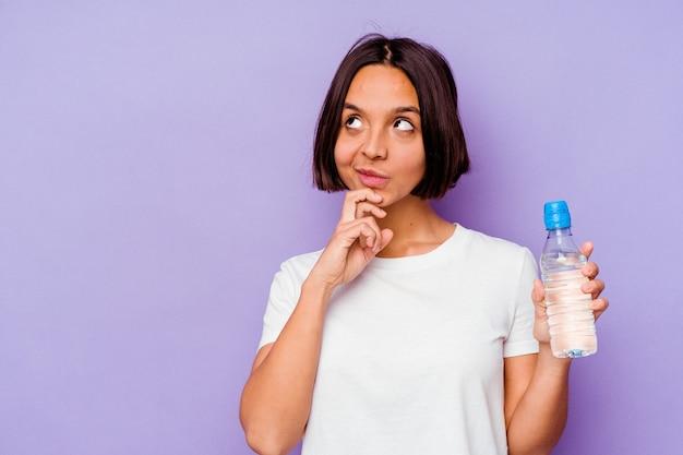 Joven de raza mixta sosteniendo una botella de agua aislada sobre fondo púrpura mirando hacia los lados con expresión dudosa y escéptica.