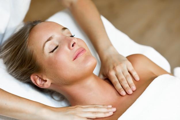 Joven recibiendo un masaje de cabeza en un centro de spa.
