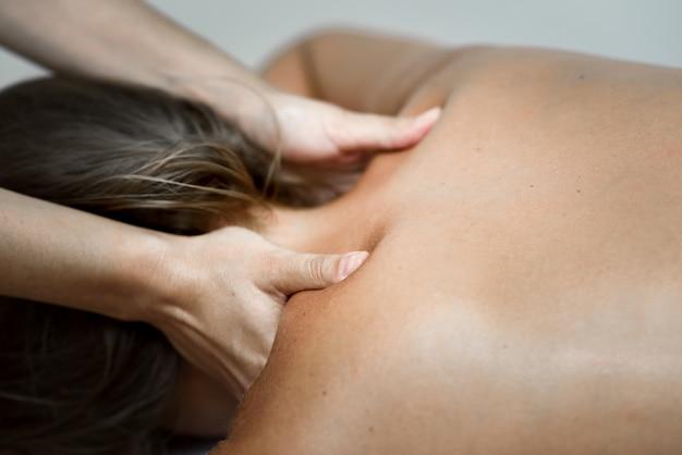 Joven recibiendo un masaje de espalda en un centro de spa.