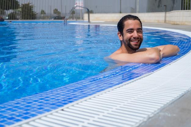 Joven relajado en la piscina