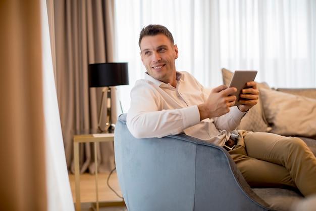 Joven relajante en casa usando tableta leyendo en la sala de estar cerca de la ventana