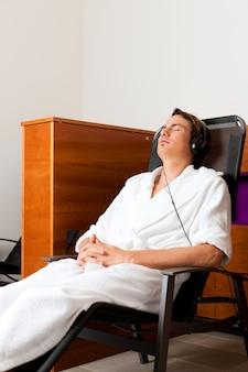 Joven relajante en el spa con música