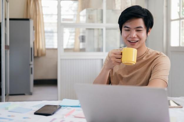 Joven relajante con una taza de café y usando la computadora portátil en casa