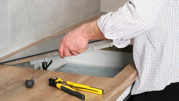Un joven reparador instala una placa de inducción negra en una moderna cocina blanca de estilo escandinavo con una pared de hormigón. hombre electricista, hágalo usted mismo. tareas del hogar.