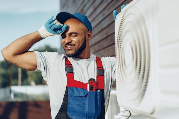 Joven reparador negro comprobando una unidad de aire acondicionado exterior