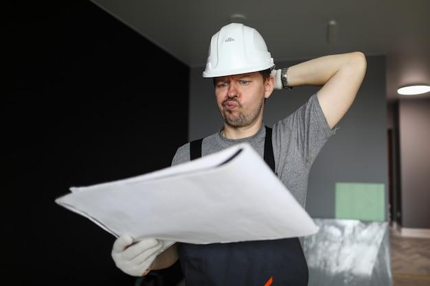 Joven reparador de pie en un piso vacío, mirando el plan de construcción y sintiéndose frustrado