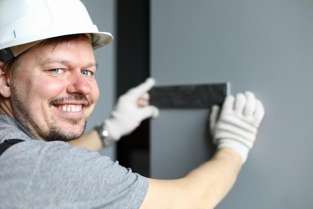 Joven reparador sonriente en casco, guantes y combinación de prueba uniforme especial de colores materiales y mirando a cámara sobre fondo de paredes grises. reparador profesional durante el concepto de trabajo.