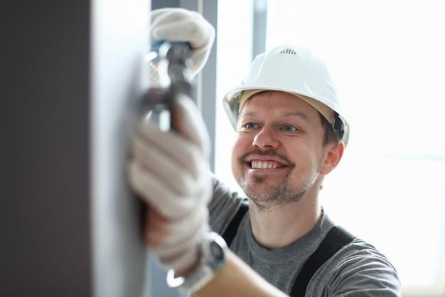 Joven reparador sonriente en casco, guantes y uniforme especial fijación y reparación de detalles de la casa en la pared sobre fondo de ventanas de luz. reparador profesional durante el concepto de trabajo.