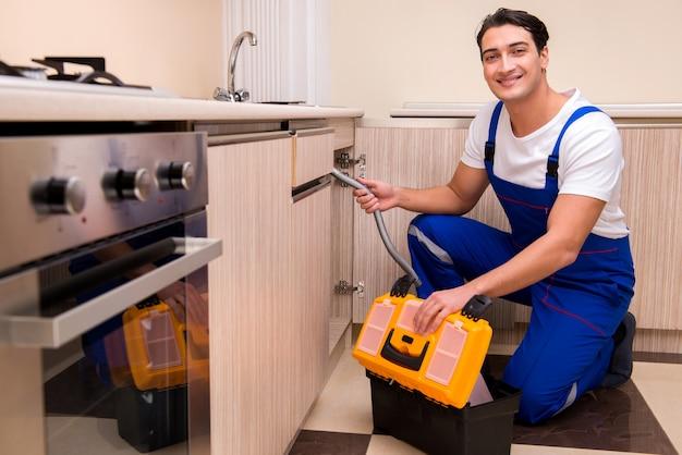 Joven reparador trabajando en la cocina