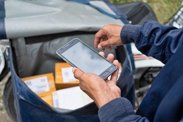 Joven repartidor moderno con smartphone en tiempo de trabajo de entrega.