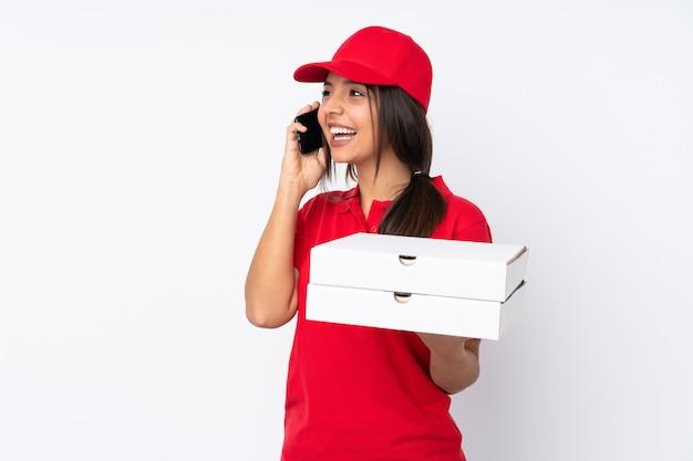 Joven repartidor de pizzas sobre blanco manteniendo una conversación con el teléfono móvil