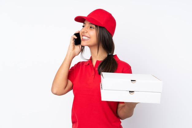 Joven repartidor de pizzas sobre pared blanca aislada con café para llevar y un móvil