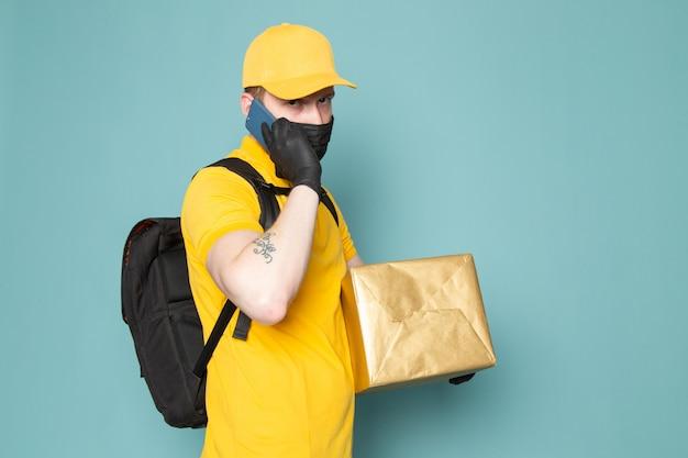 Joven repartidor en polo amarillo gorra amarilla jeans blancos mochila y máscara estéril negra sosteniendo una caja en azul