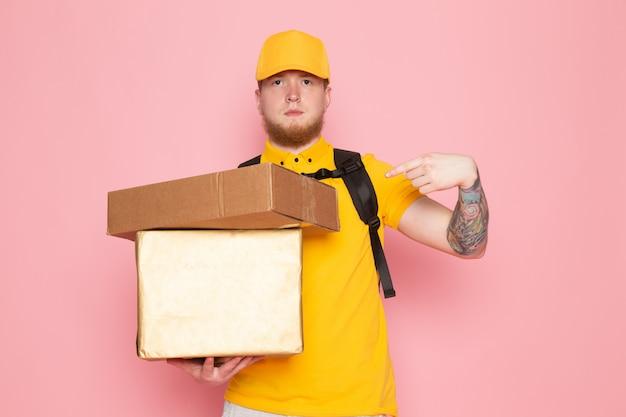 Joven repartidor en polo amarillo gorra amarilla jeans blancos sosteniendo una caja en rosa